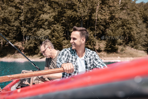 Two men sitting in rowboat and catching fish - Stock Photo - Images