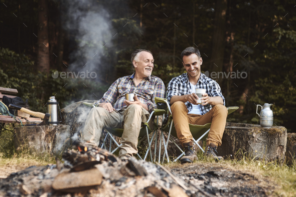 Two fishermen camping in forest - Stock Photo - Images