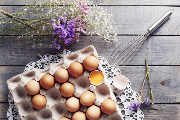 Half broken egg with whole raw eggs in protective box - Stock Photo - Images