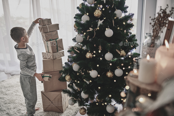 Boy stacking christmas presents next to a christmas tree - Stock Photo - Images