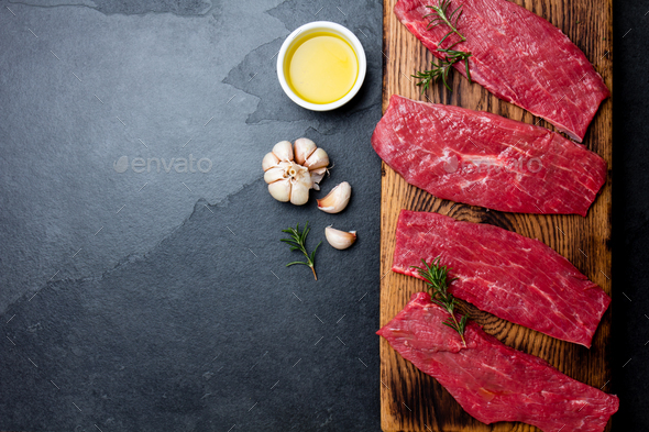 Beef tenderloin on wooden board, spices, herbs, oil on slate gray background. - Stock Photo - Images