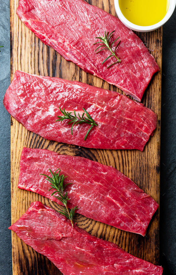 Fresh raw meat beef steaks. Beef tenderloin on wooden board, spices, herbs, oil - Stock Photo - Images