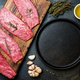 Beef tenderloin in cast iron pan on wooden board, spices, herbs, oil on slate gray background - PhotoDune Item for Sale