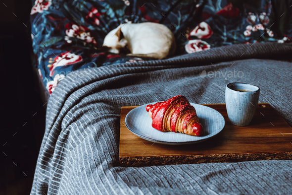 Cherry croissant with a cup of espresso on a wooden tray in a bed - Stock Photo - Images