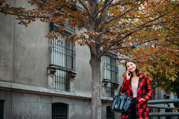 pretty young woman walking on the street using smartphone - Stock Photo - Images