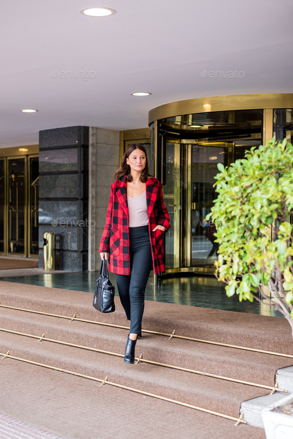 pretty young woman walking leaving an Hotel wearing autumn elegant clothes - Stock Photo - Images