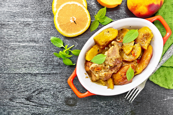 Turkey with peaches in pan on dark board top - Stock Photo - Images