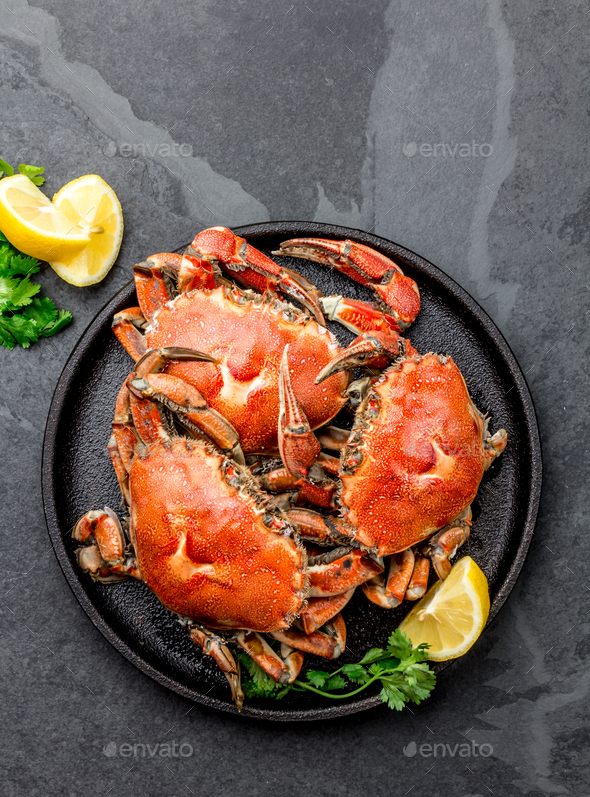 Cooked crabs on black plate served with white wine, black slate background, top view - Stock Photo - Images
