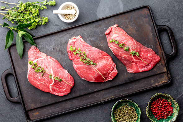 Raw beef steaks with herbs and spices on cast iron frying board, top view. - Stock Photo - Images