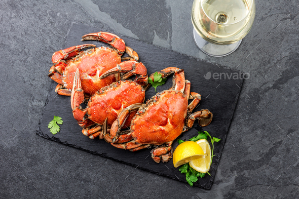 Cooked crabs on black plate served with white wine, black slate background, top view. - Stock Photo - Images