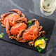 Cooked crabs on black plate served with white wine, black slate background, top view. - PhotoDune Item for Sale