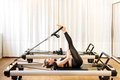 Woman doing short spine pilates exercises - PhotoDune Item for Sale