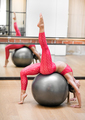 Woman exercising on a stability ball in a gym - PhotoDune Item for Sale