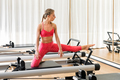 Woman doing leg stretching exercises in a gym - PhotoDune Item for Sale