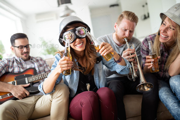 Group of friends at home enjoying singing and playing guitar - Stock Photo - Images