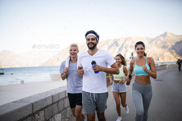 Happy fit people running and jogging together in summer sunny nature - Stock Photo - Images
