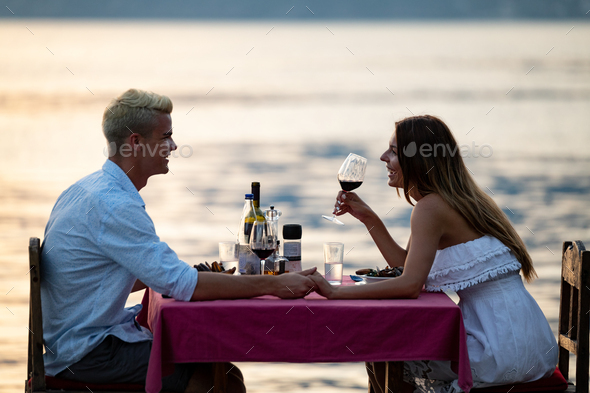 Young couple have romantic evening on sea beach - Stock Photo - Images