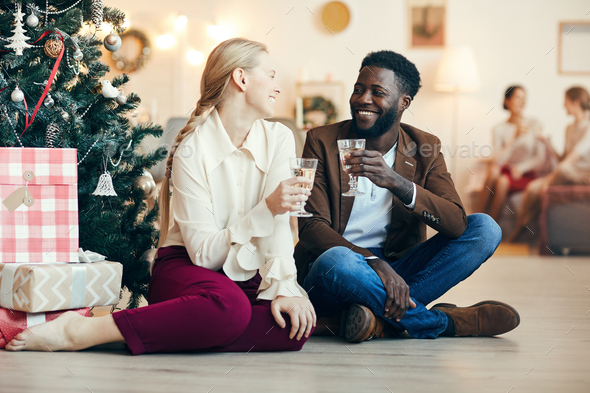Couple Sitting by Christmas Tree - Stock Photo - Images