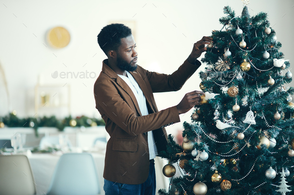Modern African Man Decorating Christmas Tree - Stock Photo - Images
