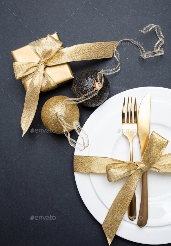 Table setting, xmas, new year. Gold cutlery on white set of dishes, black background - Stock Photo - Images