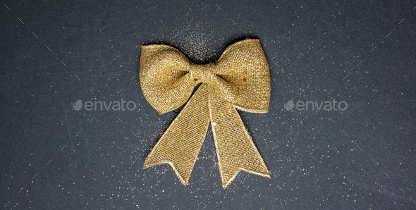 Golden present bow on black background, top view - Stock Photo - Images