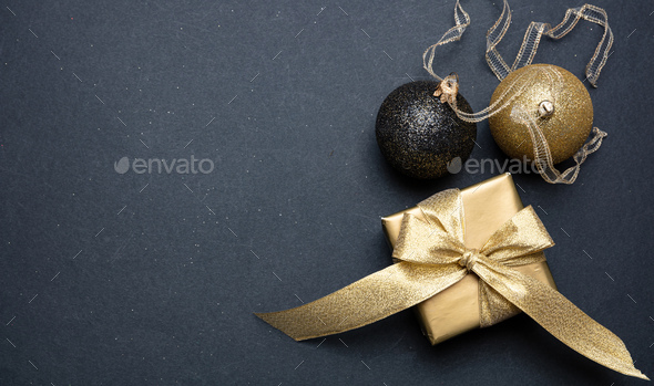 Xmas present and bauble shiny gold color against grey black background - Stock Photo - Images