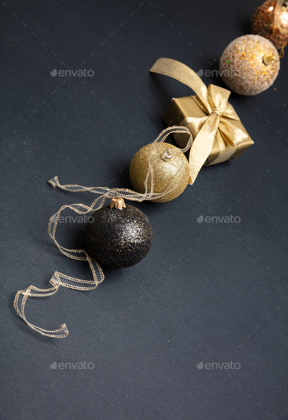 Xmas baubles shiny gold color against grey black background - Stock Photo - Images