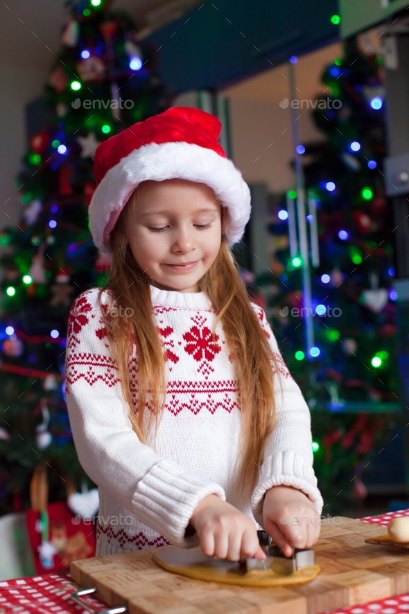Adorable little girl baking gingerbread cookies for Christmas - Stock Photo - Images