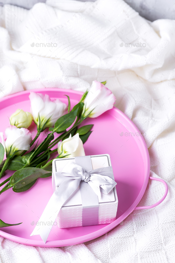 Gift box and pastel flowers eustoma for Valentines or Mothers day on pink tray on bed . Flat lay - Stock Photo - Images