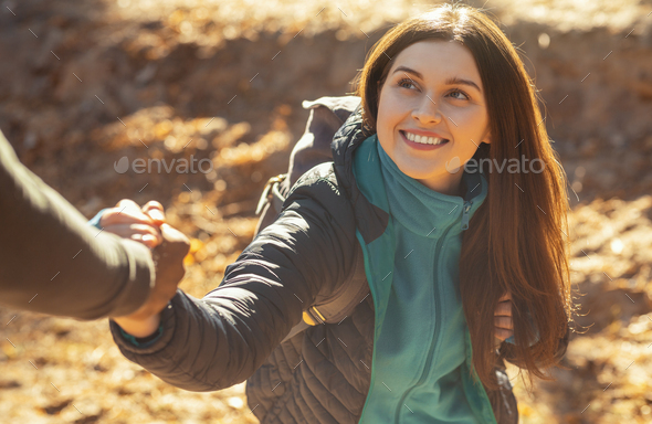 Portrait of pretty girl supported by man while hiking - Stock Photo - Images