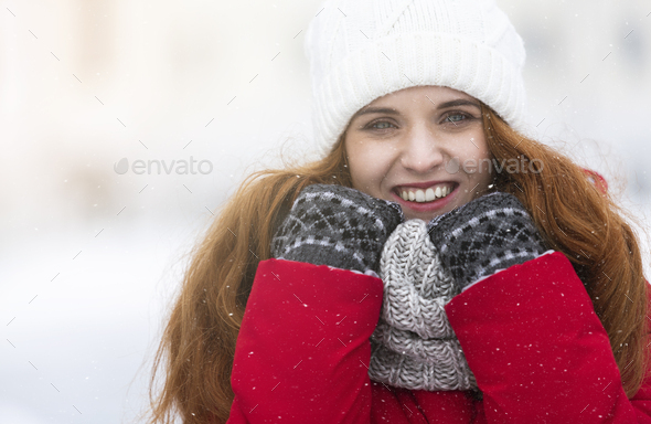 Cheerful young girl in warm clothes enjoying snowy winter day - Stock Photo - Images