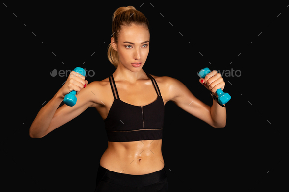 Determined Woman Exercising With Dumbbells, Studio Shot - Stock Photo - Images