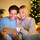 Couple looking at old photos on tablet next to Christmas tree - PhotoDune Item for Sale