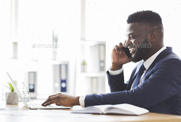 Smiling businessman having conversation with clients, typing on laptop - Stock Photo - Images