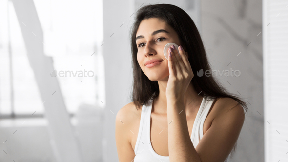 Young Woman Removing Makeup Using Cotton Pad In Bathroom - Stock Photo - Images