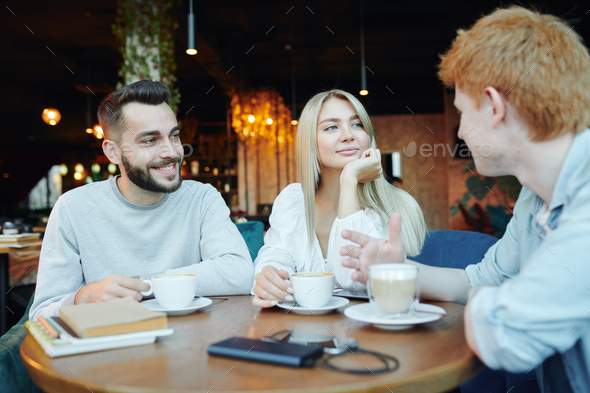 Happy young heterosexual couple chatting to their friend by cup of cappuccino - Stock Photo - Images