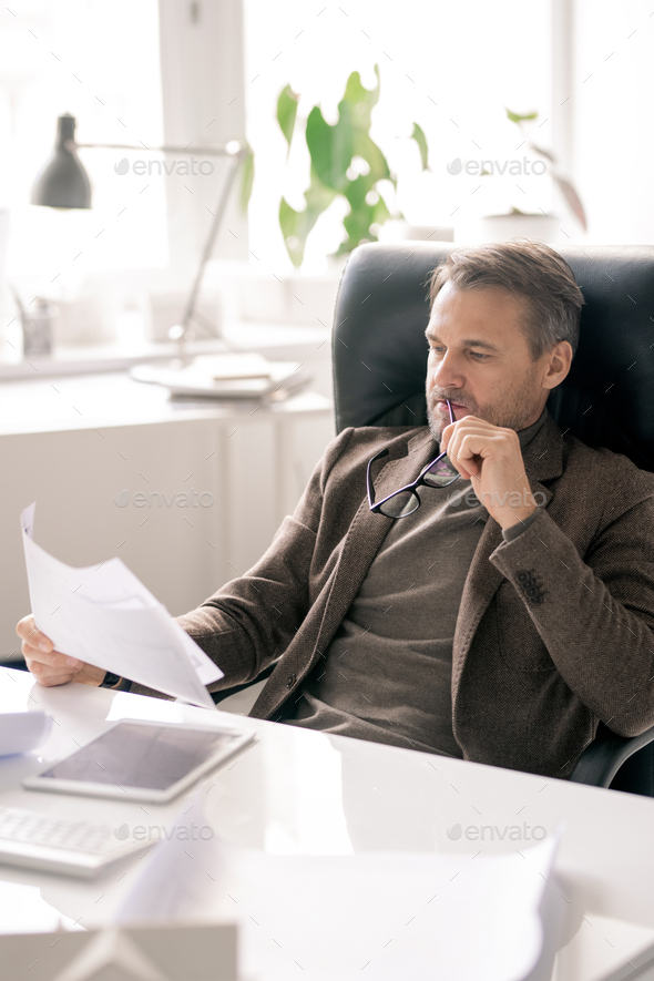 Serious director of company sitting by desk and looking through paper - Stock Photo - Images