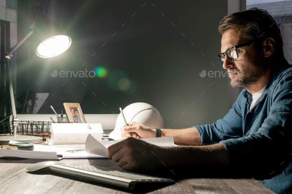 Serious architect working over new project in office late in the evening - Stock Photo - Images