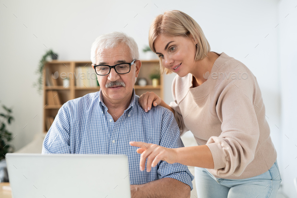 Young woman pointing at laptop display while explaining something to her father - Stock Photo - Images