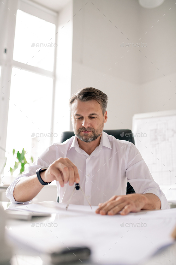 Mature engineer with dividers making new sketch of architectural construction - Stock Photo - Images