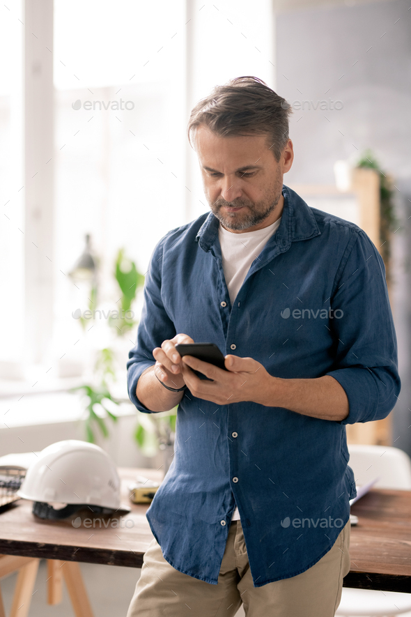 Contemporary mobile engineer with smartphone scrolling through contacts - Stock Photo - Images