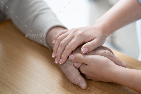 Hands of young affectionae and careful woman holding that of her senior father - Stock Photo - Images