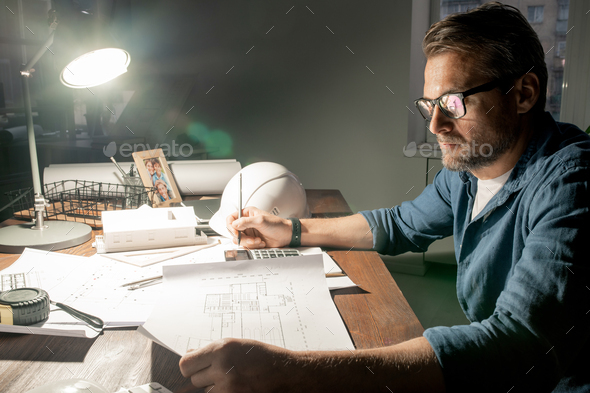 Serious engineer decided to stay at work for night to check sketches - Stock Photo - Images
