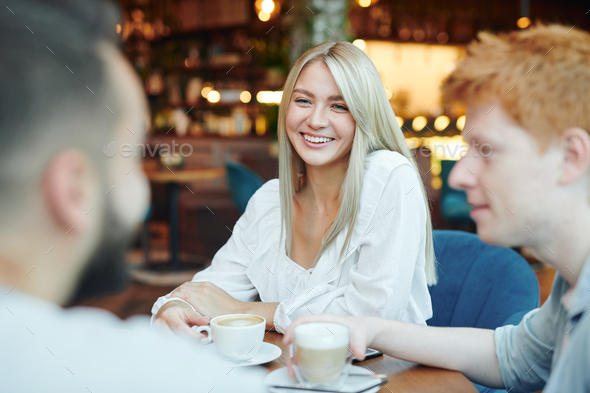 Happy blonde girl with toothy smile having cup of cappuccino with two guys - Stock Photo - Images