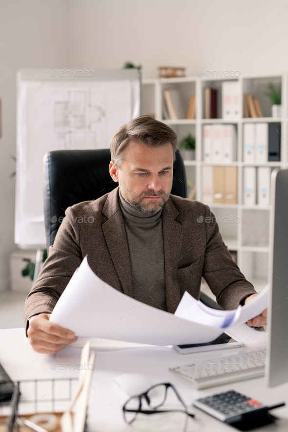 Serious mature architect in formalwear looking through papers or blueprints - Stock Photo - Images