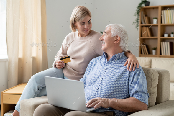 Pretty casual woman with credit card looking at her retired father with laptop - Stock Photo - Images