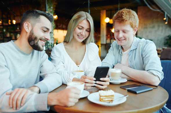Pretty blonde girl with smartphone showing two happy guys her new photos in cafe - Stock Photo - Images