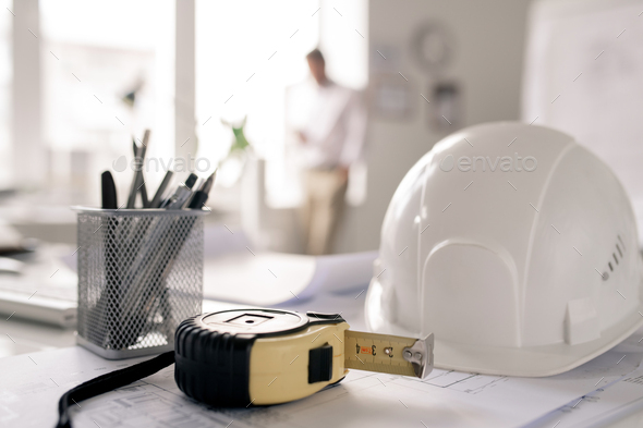 Workplace of engineer with hardhat, measuring tape, bunch of pencils and sketch - Stock Photo - Images