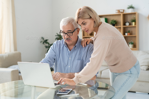 Young woman in casualwear and her senior father looking at laptop display - Stock Photo - Images