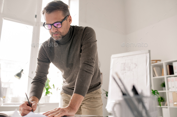 Confident engineer bending over papers while drawing new sketches in office - Stock Photo - Images